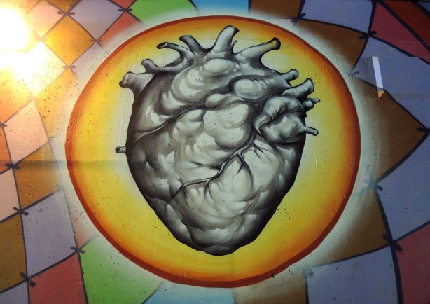 part of a mural on a concrete wall under a bridge under the 401 in Toronto, an anatomical painting of a heart that looks #D, surrounded by a yellow circle