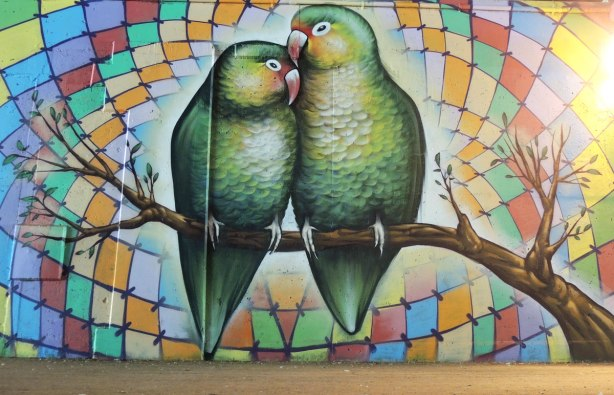 part of a mural on a concrete wall under a bridge under the 401 in Toronto, two green lovebirds on a tree branch, with a background of multicoloured diamond shapes arranged concentrically
