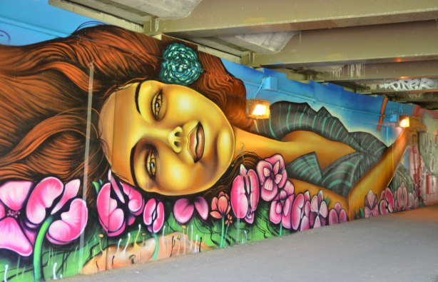 part of a mural on a concrete wall under a bridge under the 401 in Toronto, looking along the south end of the wall with a woman's head lying on a bed of pink flowers in the foreground.