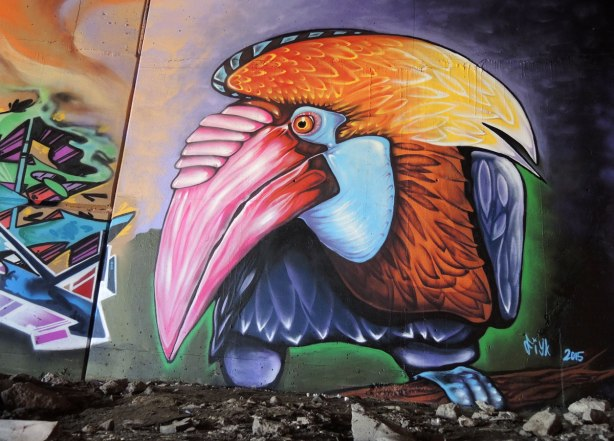 part of a mural under the 401 in Toronto,  a large toucan head with a pink beak and yellow and orange head plume