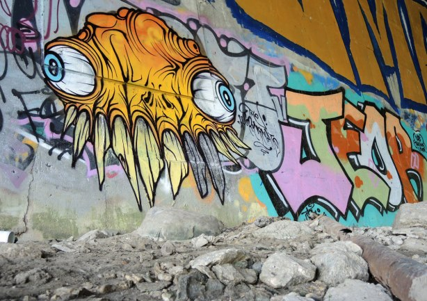a yellow grominator street art painting, bulging veiny eyes and many crooked sharp teeth