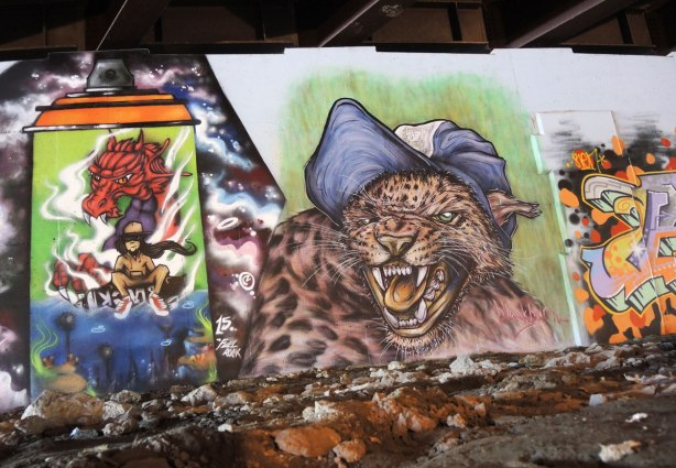 part of a mural under a bridge - two paintings.  On the right is a very realistic growling wild cat (bobcat) wearing a blue and white baseball cap.  On the left is a large spray paint can with a picture of a seated person on it.   A large red dragon is behind that person, although the head of the dragon is coming forward above the person's head
