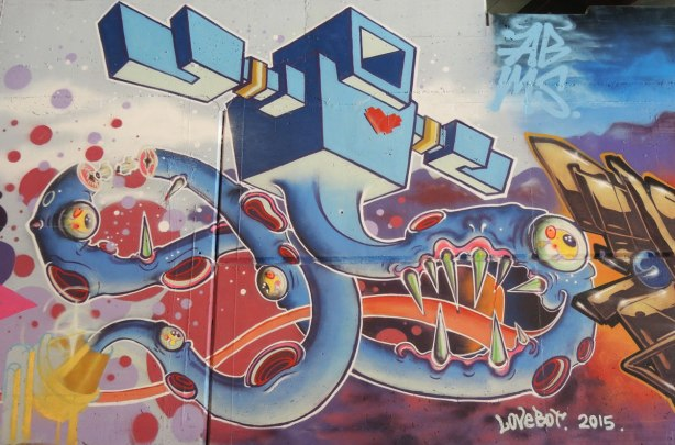 part of a mural under a bridge - lovebot, a giant light blue lovebot swirls on a wall