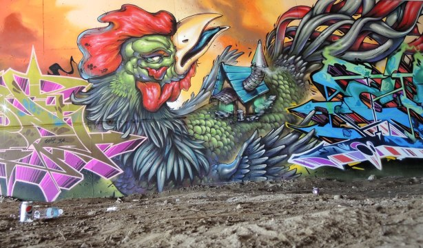part of a mural under the 401 in Toronto, a very large rooster in profile with its tail feathers reaching to the top right of the picture