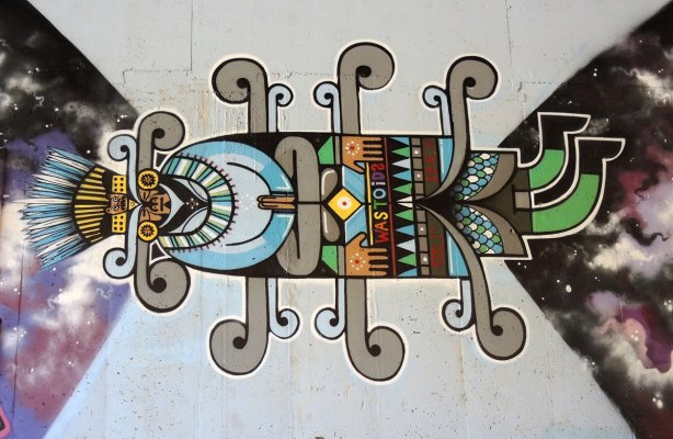 part of a mural under the 401 in Toronto,  a human like figure, with South American influences, lying on its side, the word WASTOID written across its belt