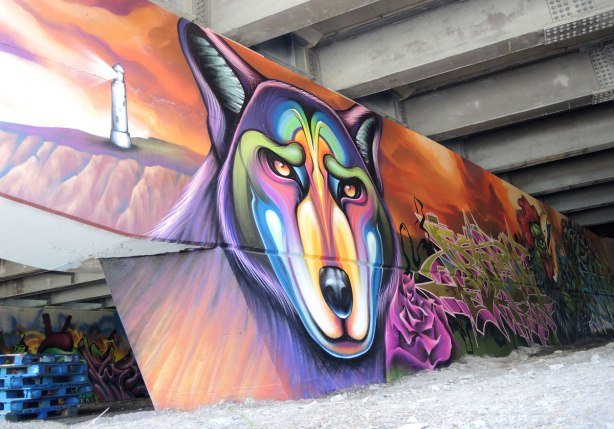 part of a mural under a bridge - a large multi coloured wolf head