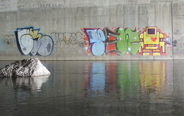 street art on a concrete bridge support, reflected in the river beside it is a yellow lovebot as well as some large tag letters