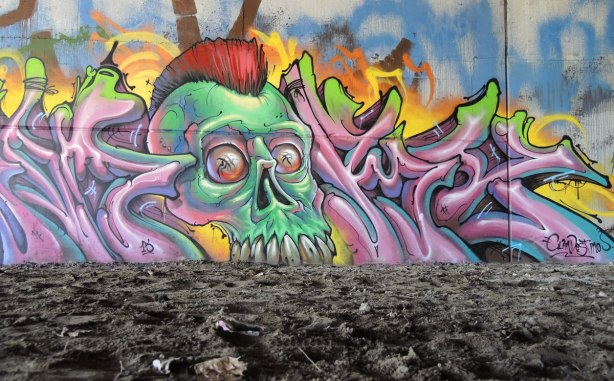 mural painting on a wall, looks like a green zombie head coming out of the ground.  photo taken from a low angle