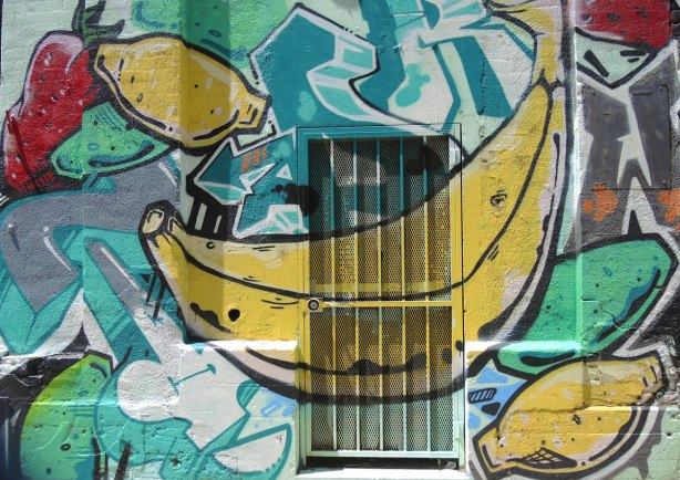 Mural on the back of a building, including over a door with metal grille and bars.  A very big banana, some strawberries and some lemons are in the picture.