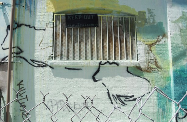 metal barred window with Keep Out sign on it, a mural of running animals drawn as outline figures, with the top of a chain link fence in the very foreground of the picture.