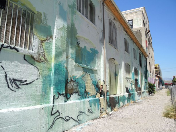 Old brick building painted white then covered with a mural in pale blues and greens.