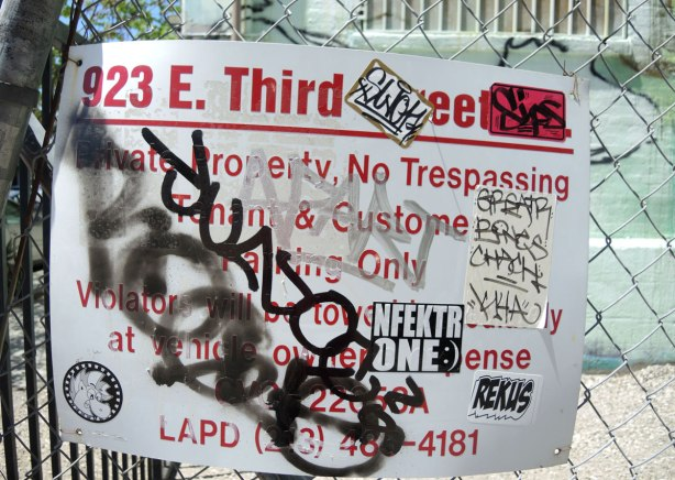 No trespassing sign at 923 East Third Street in LA, it has 5 or 6 stickers on it as well as some scribbles in black