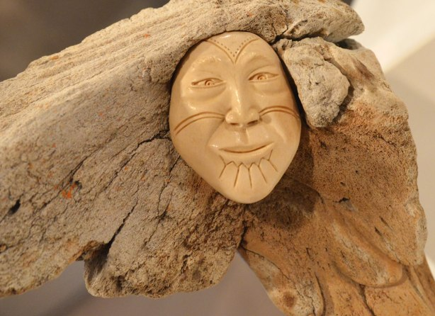 part of a sculpture by Manasie Akpaliapik made of bone, ivory and stone, a man's face