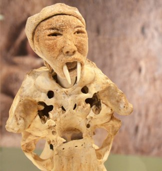 part of a sculpture by Manasie Akpaliapik made of bone, ivory and stone, a man like creature with a man's face but with walrus tusks
