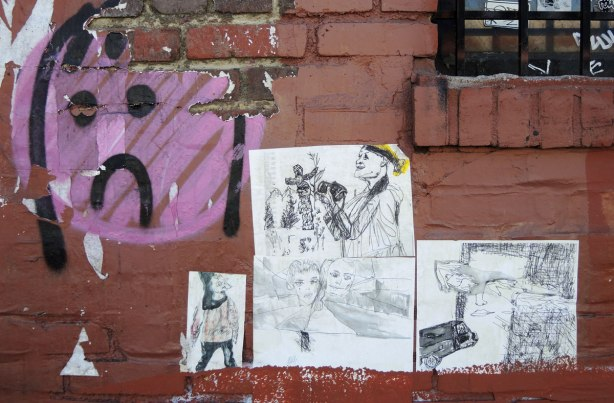 wheatpaste street art on the exterior walls of an old red brick building (intircate black and white drawings of people, as well as a painted pink and black sad face