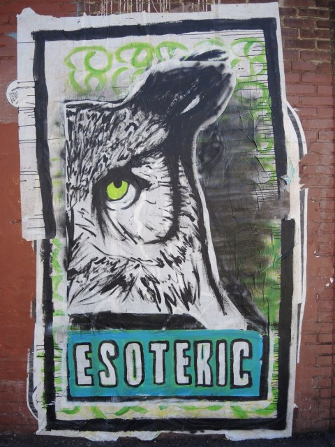 wheatpaste street art on the exterior walls of an old red brick building - an owl face along with the word 'esoteric'