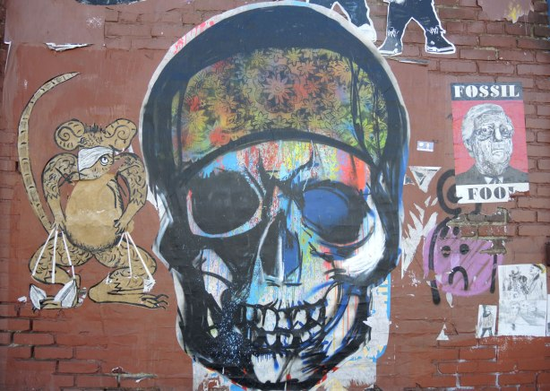 wheatpaste street art on the exterior walls of an old red brick building - a skull with a multicoloured head band, and a goldish brown monkey