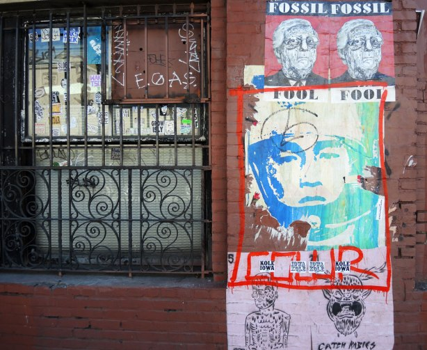 wheatpaste street art on the exterior walls of an old red brick building - two small posters with the line 'fossil fuels' and picture of an older man, the astronaut pic, and two smaller black and white pics at the bottom