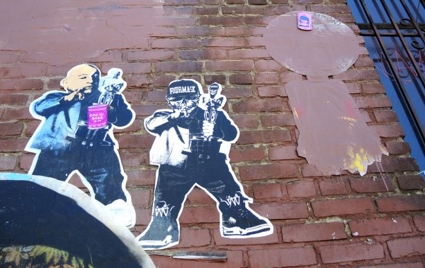 wheatpaste street art on the exterior walls of an old red brick building - two young men
