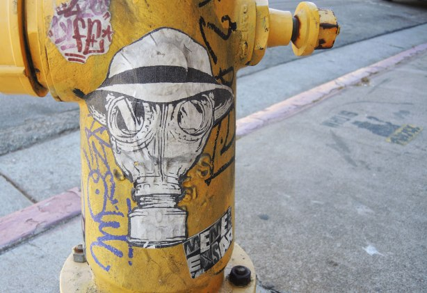 wheatpaste street art on the exterior walls of a yellow fire hydrant - a man's head, wearing a gas mask and a hat