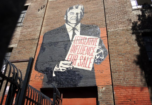 street art piece of Ronald Regan holding a sign that says 'Legislative Influence for sale'