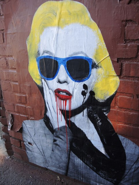 A wheatpaste Marilyn Munroe with very yellow hair, blue rimmed dark sunglasses and red lipstick that is running.  Three large black dots are on one of her cheeks.