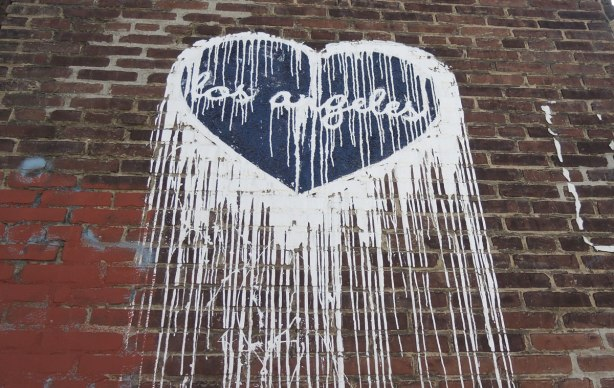 graffiti dark blue heart with the 'words los angeles' written in white cursive lettering.  White paint runs down from the sides of the heart.