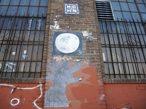 wheatpaste street art on the exterior walls of an old red brick building - one is a full moon, another is a tree drawn with squiggly lines that make the texture of the bark