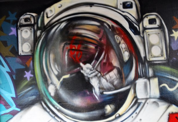 street art painting under a railway bridge - astronaut's helmet