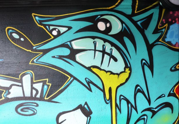 street art painting under a railway bridge - an ugly blue creature with nasty look on his face, yellow stuff oozing from the corner of his mouth