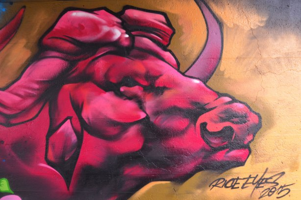 street art painting under a railway bridge - a pink, maroon and red bull
