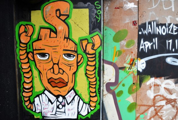 street art painting under a railway bridge - a mn with orange skin, large head and twisted pipes for arms.  A bis S is coming out of the top of his head