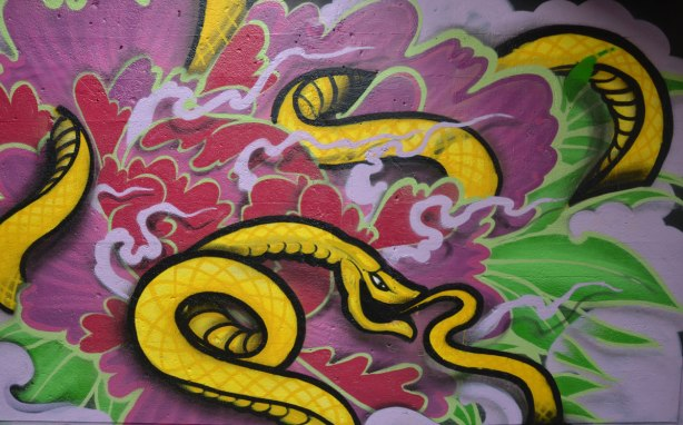 street art painting under a railway bridge - a long yellow snake curld up amongst purple and red swirls