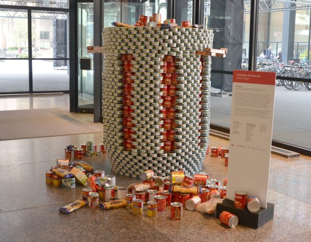 sculptures on display that were entered in a contest in support of the Daily Food Bank, sculptures made of canned food in a theme pertaining to hunger awareness - an oversized trash can overflowing with cans of food. The trash can is made of gray coloured cans