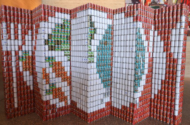 sculptures on display that were entered in a contest in support of the Daily Food Bank, sculptures made of canned food in a theme pertaining to hunger awareness - a red folded wall with a white plate, white knife and white fork on it.