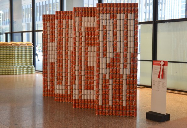 sculptures on display that were entered in a contest in support of the Daily Food Bank, sculptures made of canned food in a theme pertaining to hunger awareness - from one angle this sculpture is a red wall with the word HUNGRY written on it in block white letters