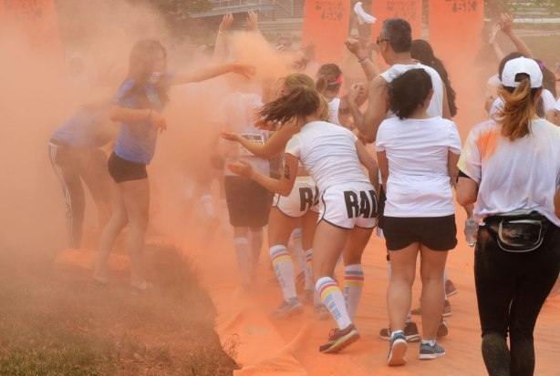 running through clouds of orange powder, color me rad run - a woman in blue is throwing orange powder at a group of runners who are wearing white.  Two of the women are wearing white shorts with big letters spelling RAD on the back