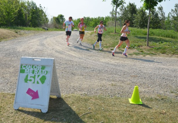 Four runners running past a direction sign on the color me rad run