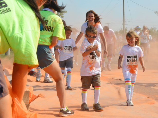 running through clouds of orange powder, color me rad run - three kids, the boy in front is clutching his arms to his chest and he is smiling.  A girl is beside him and smiling as he gets covered with orange powder