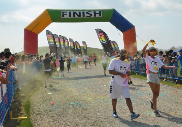 color me rad run finish line with a few people crossing over it at the end of the race.  People are standing behind blow metal fences to watch the finishers.
