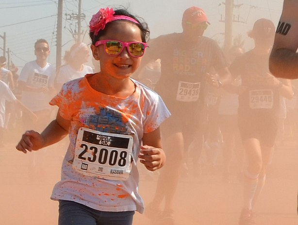 A young girl with a pink flower on her hair band, and wearing pink sunglasses is running through a cloud of orange powder, a couple of men are in the haze behind her