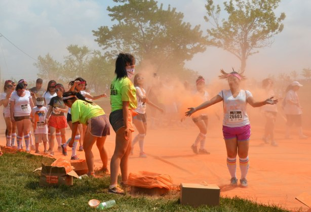 A young woman in pink shorts is jumping as she goes past those who are colour bombing in the color me rad run.  Her hair is standing on end.