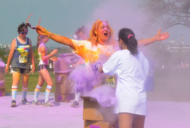 A woman with a lot of yellow and orange powder in her hair raises her arms as another woman throws purple powder at her.