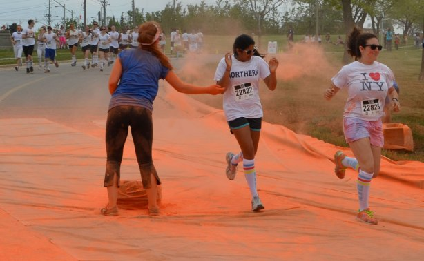 running through clouds of orange powder, color me rad run , a woman with 'Northern' written on her Tshirt is getting hit with orange powder.