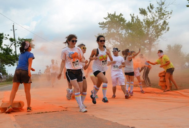 running through clouds of orange powder, color me rad run - a group of runners