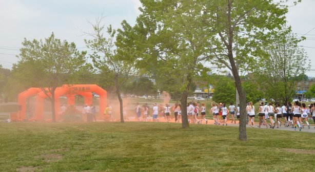 The orange powder station from a distance in the color me rad run.  Many runners are heading towards it.