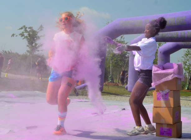 One woman is throwing purple powder at another woman