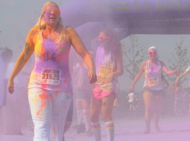 Three women are walking through a cloud of purple powder, color me rad run
