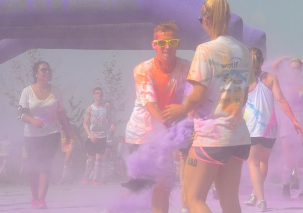 A man in yellow sunglasses who is covered in orange and red powder is throwing purple powder at his girlfriend