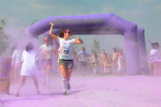A woman runs out of a cloud of purple powder, her arms raised, many people behind her in the haze, color me rad run Toronto May 2015